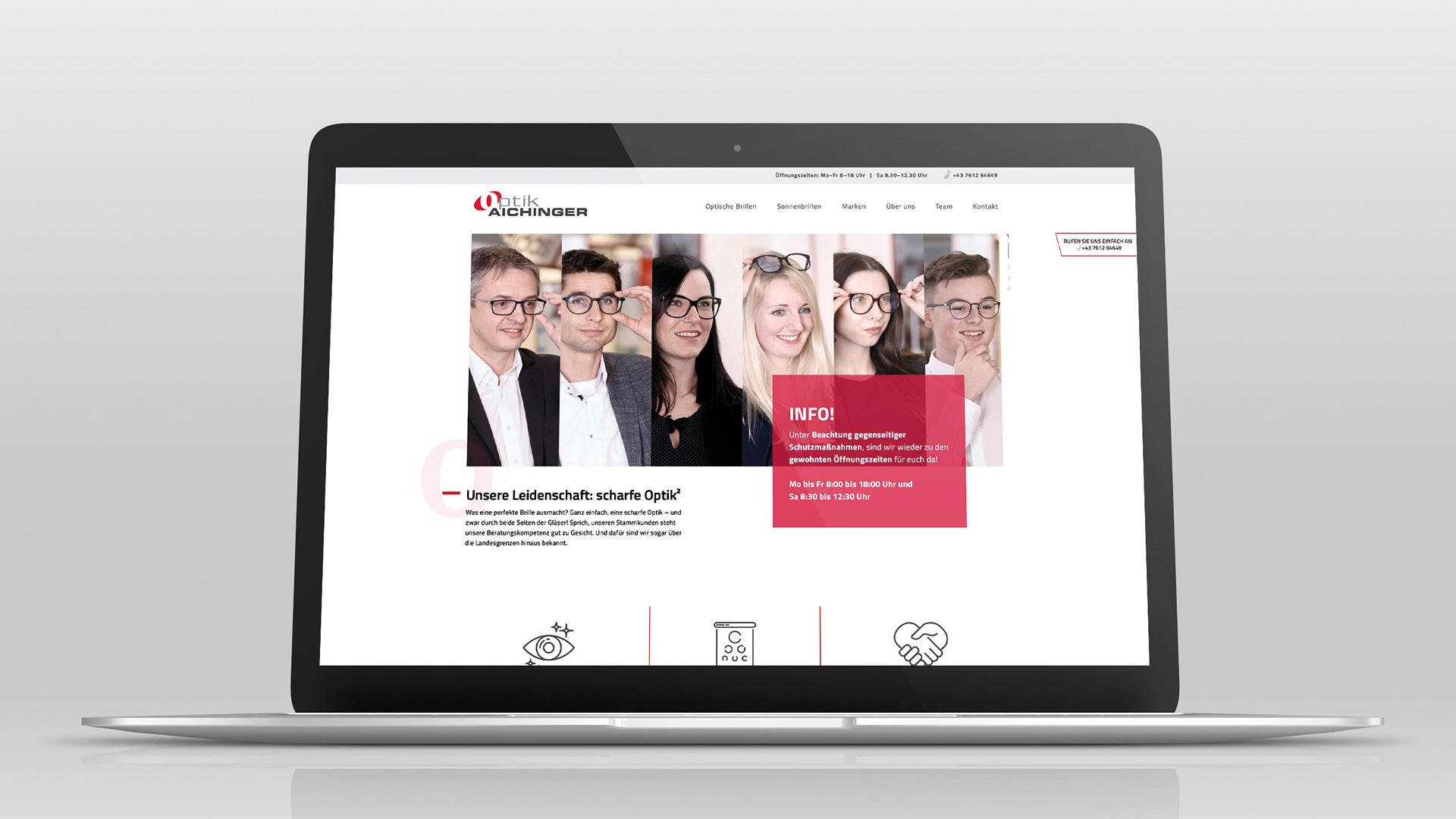 Ein Laptop zeigt das Webdesign von Optik Aichinger mit diversen Brillenträgern als Modell
