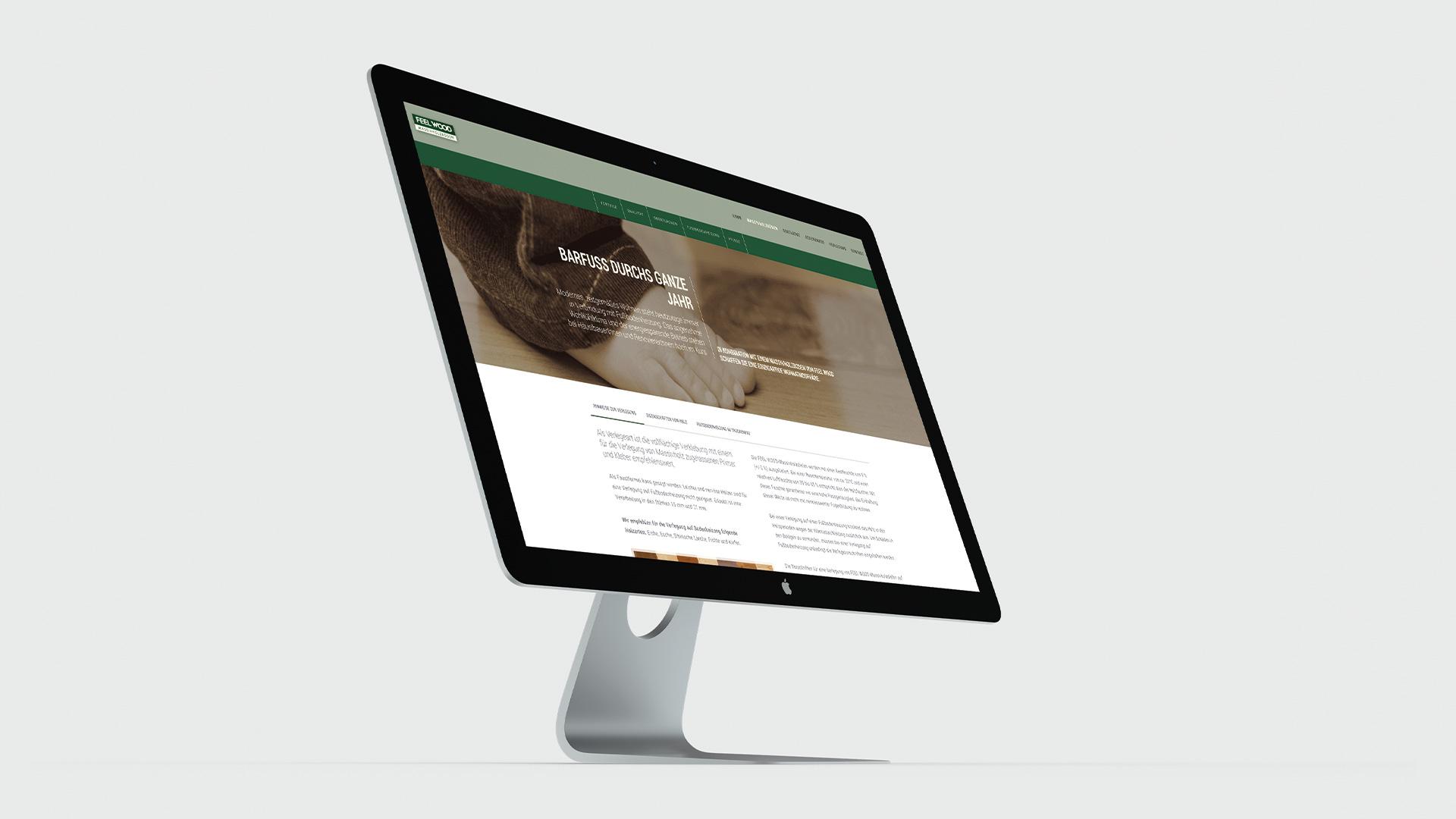 Desktop mit Webdesign von Feel Wood das einen Barfuss zeigt