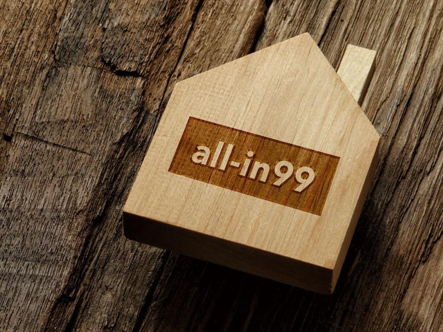 Kleines Holzhaus mit all-in99 Schriftzug auf Holztisch