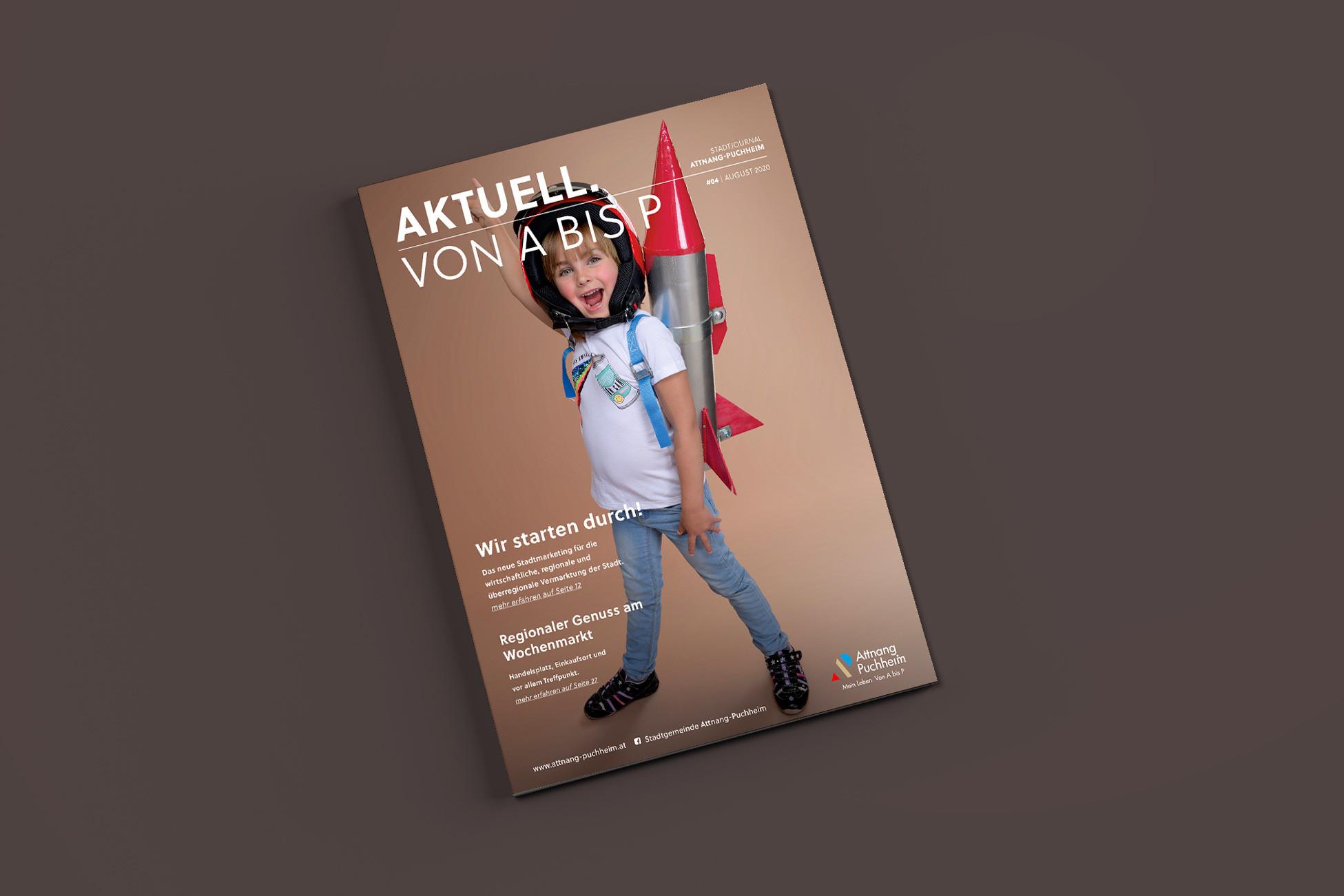 Cover vom Stadtmagazin Attnang-Puchheim mit Kind am Cover das eine Spielzeug-Rakete am Ruecken traegt