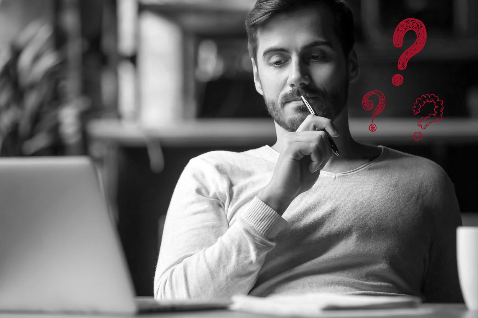 Mann in Denkerpose vor Laptop mit roten Fragezeigen als Sinnbild für die Leadgenerierung versus Branding