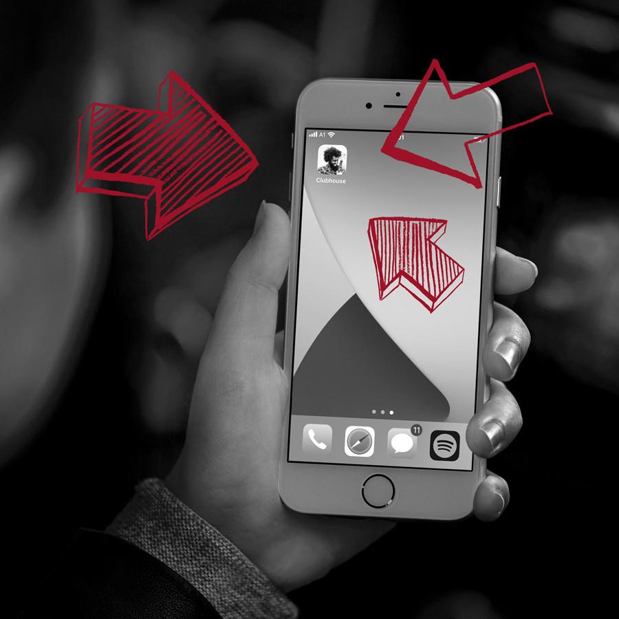 Graues Smartphone in einer Hand mit roten Pfeilen auf Profilbild bei Clubhouse zeigend