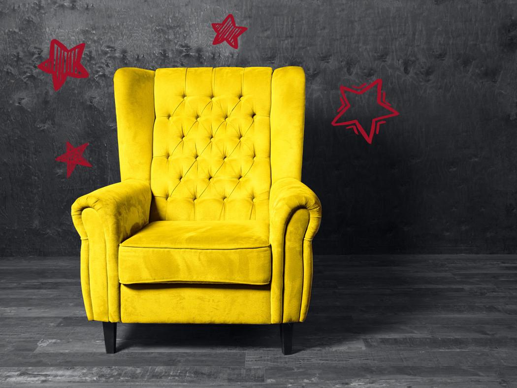Gelber Ohrensessel mit roten Sternen auf grauem Hintergrund steht für die Pantone Farben 2021