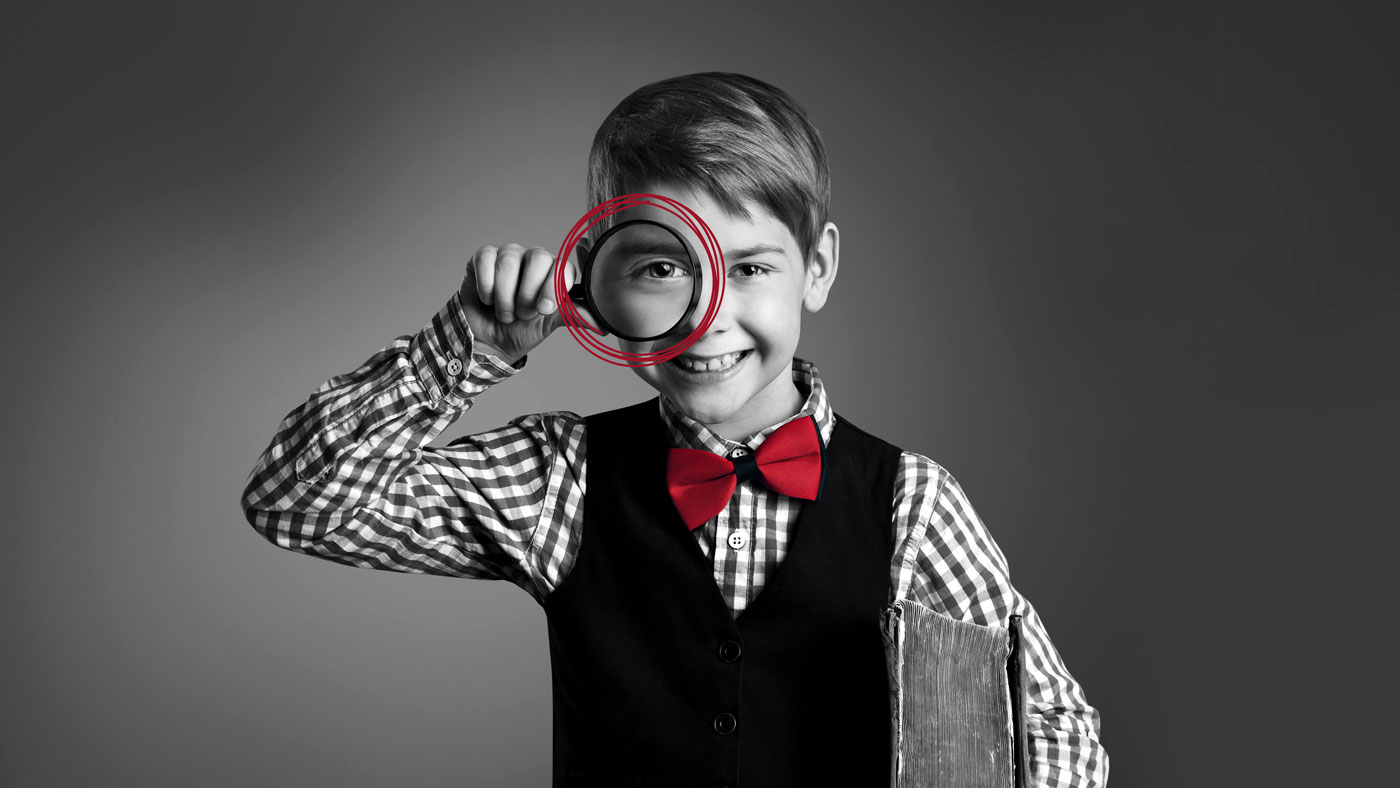 Ein Junge mit einer Lupe als Sinnbild für die Bedeutung der SEO-Texte bei der Suche